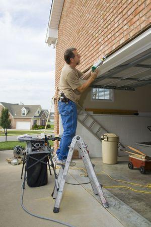 caulking: Carpenter caulking cracks between garage door frame and brick