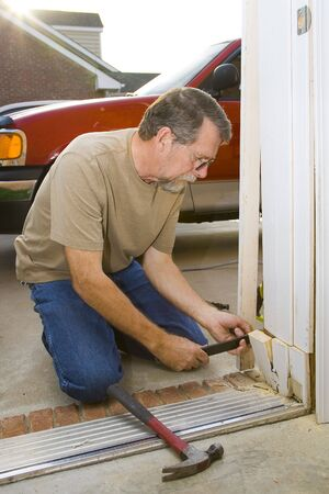 Carpenter repairing exterior door casing, weather & insects have contributed to rot at the bottom of casing  Stock Photo - 3593890
