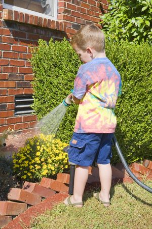 Young child watering flowers around the house, drought is taking it's toll