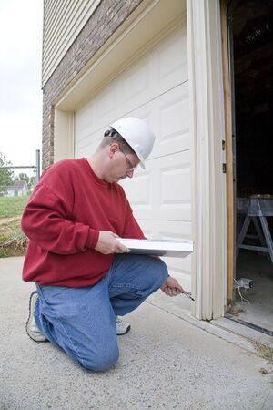 aide a domicile: Home Inspecteur de la recherche d'�ventuels probl�mes pour un acheteur potentiel, a pourri � ossature de bois sur l'ext�rieur cadre de la porte Banque d'images