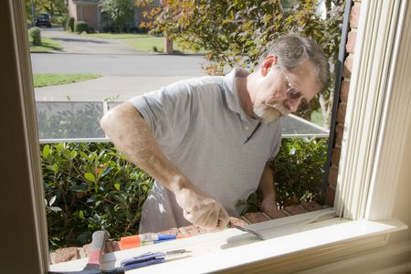 Carpenter cutting wood needed to replace rotten wood on exterior of home