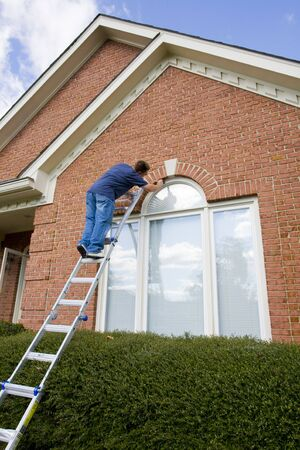 compete: Contract painter painting exterior trim to speed up selling of home,used houses have to compete with new homes on the market Stock Photo