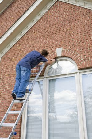 Contract painter painting exterior trim to speed up selling of home,used houses have to compete with new homes on the market Stock Photo