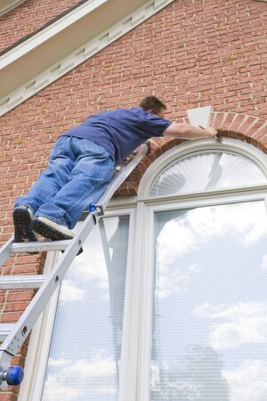 house painter: Contract painter painting exterior trim to speed up selling of home,used houses have to compete with new homes on the market Stock Photo