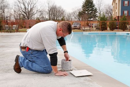 Service man cleaning pool filters, removing leaves that have fallen in pool this fall Stock Photo