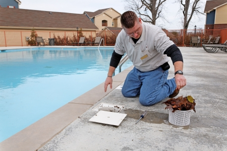 Service man cleaning pool filters, removing leaves that have fallen in pool this fall photo