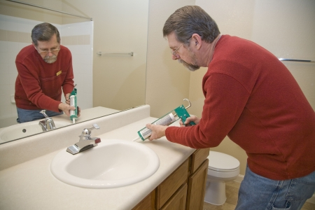 seeping: Contractor caulking around toilet to keep moisture from seeping