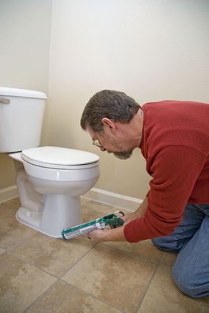 Contractor caulking around toilet to keep moisture from seeping