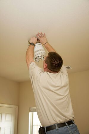 fixture: Electrician installing new light fixture and fan combination