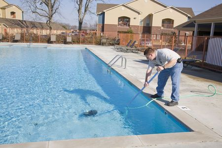 maintenance man: Service man cleaning pool filters, removing leaves that have fallen in pool this fall Stock Photo
