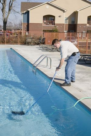 active adult community: Service man cleaning pool filters, removing leaves that have fallen in pool this fall Stock Photo