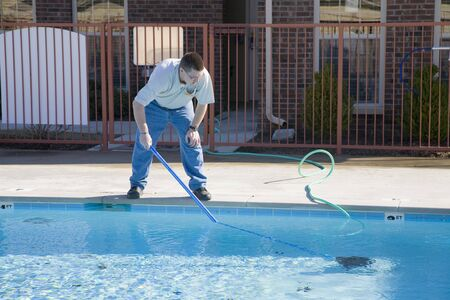 service: Service man cleaning pool filters, removing leaves that have fallen in pool this fall Stock Photo
