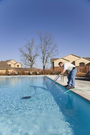 swimming pool home: Service man cleaning pool filters, removing leaves that have fallen in pool this fall Stock Photo
