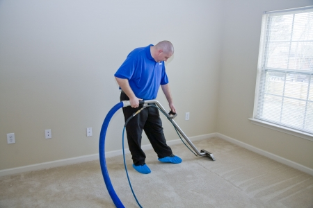 house cleaner: Man cleaning carpet with commercial cleaning equipment