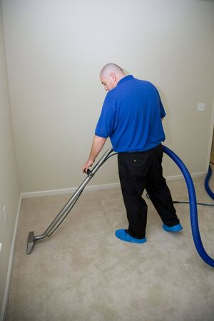 Man cleaning carpet with commercial cleaning equipment photo
