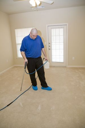 Man cleaning carpet with commercial cleaning equipment, He is treating stains before using steamer