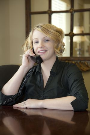 qualify: Receptionist welcoming customers at front desk, Explaining what they will to qualify for an apartment lease