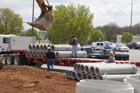 18 wheeler: Workers are unloading concrete drainage pipe from18 wheeler flatbed truck, getting every thing ready for new building going up