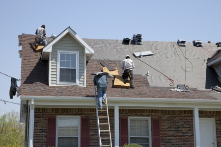 roofer: Roofers replacing damaged shingles after storm