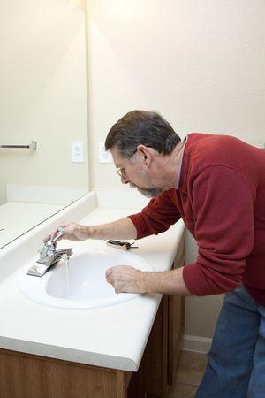 ahorrar agua: Fontanero fauset la instalaci�n de nuevas juntas para ahorrar agua y reducir la factura del agua Foto de archivo
