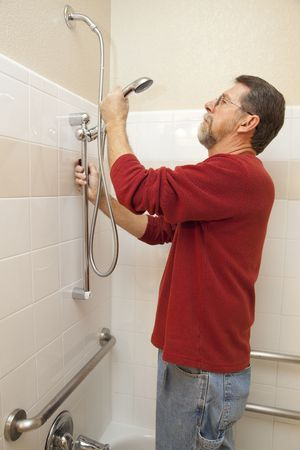 making a save: Plumber installing new shower handi-cap system to save water and cut down on water bill well making it easyer for the disabled