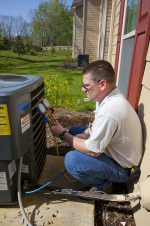 Air conditioning technician checking freon levels in a new high efficiency air conditioning unit that was installed recently