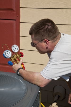 air conditioner: Air conditioning technician checking freon levels in a new high efficiency air conditioning unit that was installed recently
