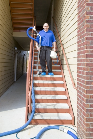 Man cleaning carpet with commercial steam cleaning equipment photo