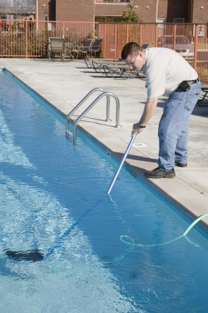 Service man cleaning pool filters, removing leaves that have fallen in pool this fall 스톡 콘텐츠