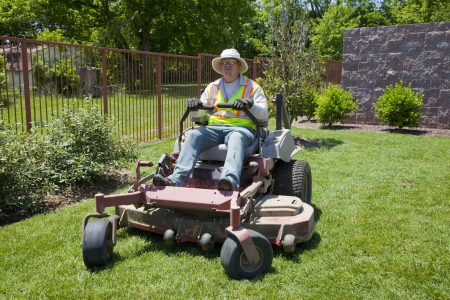 Man on commercial zero turn lawn mower, taking care of large property