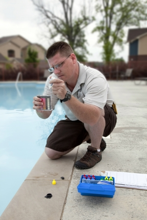hardness: Service man checking chlorine, PH and other chemical levels in community pool Stock Photo