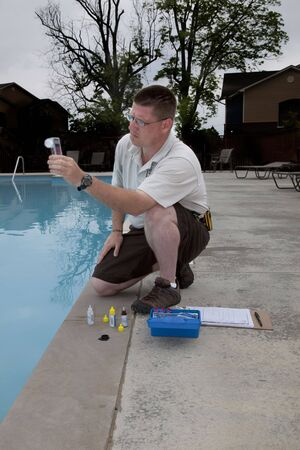 Service man checking chlorine, PH and other chemical levels in community pool early morning before pool opens Stock Photo