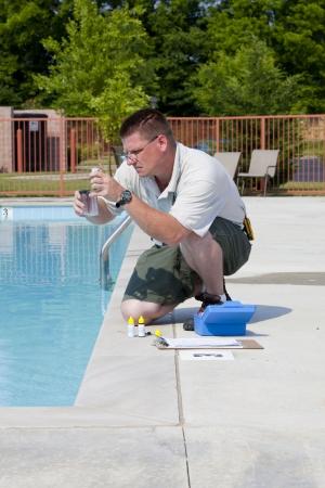 mantenimiento: Hombre de servicio de control de cloro, PH y otros qu�micos en los niveles piscina comunitaria
