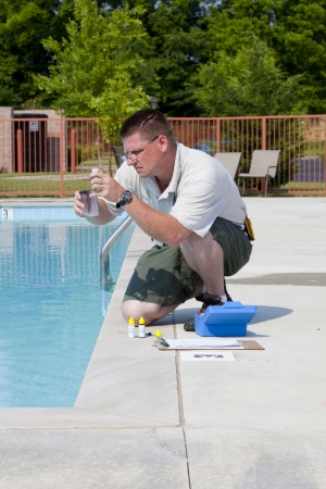 Service man checking chlorine, PH and other chemical levels in community pool Imagens