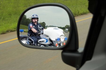 Police officer on his motorcycle watching for speeders and people runnig stop signs