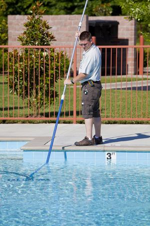 Service man checking chlorine, PH and other chemical levels and cleaning community pool