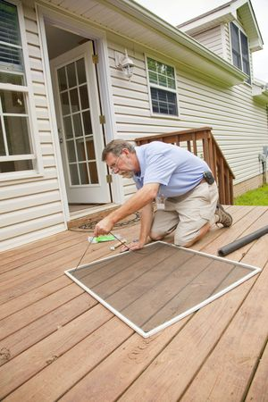 Man replacing damaged window screens on home that will be put up forsale Stock Photo