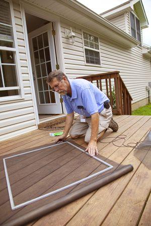 Man replacing damaged window screens on home