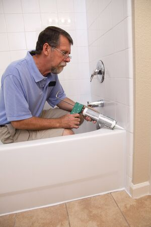 caulk: Contractor caulking around tub, sealing to prevent possible water leakage, protecting wood under tub