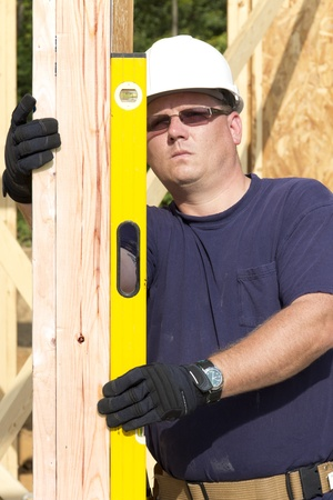 door casing: Carpenter inspecting walls for plumb, walls need to be very straight for door casing and windoes