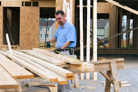 osb: Carpenter inspecting wood before selecting the next support beam