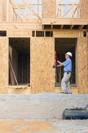 Carpenter inspecting rough door frame opening to make sure the entry is level photo
