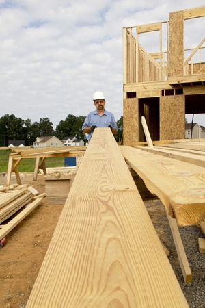 Carpenter inspecting wood before selecting the next support beam