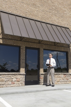 finance director: Bank finance personal inspecting new strip mall that his company financed