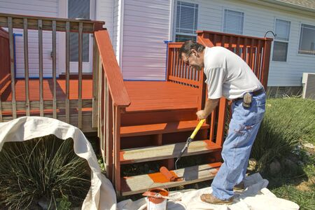 Contract painter staining deck on home to protect it from the weather Stock Photo