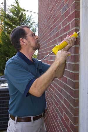 Contractor caulking exterior walls between  frame and brick, sealing to stop possible air leaks, conserving energy Stock Photo