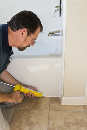 caulk: Contractor sealing tub base to keep water from seaping through the ceramic tile and rotting the floor Stock Photo