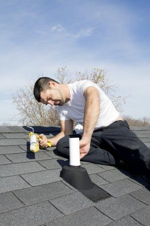 shingles: Techador reparación de fugas en los tubos de ventilación en el techo de su casa, el agua entró y dañó el techo Foto de archivo
