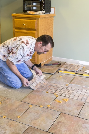 tile grout: Man installing ceramic tile in customers kitchen, getting ready to sell home