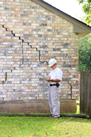 Inspector inspecting home?s foundation is experiencing settlement (collapse). Eventually the brick veneer begins to separate from door and window frames. Finally framing and roof problems occur, as well as plumbing problems. Foundation problems don?t get  Foto de archivo